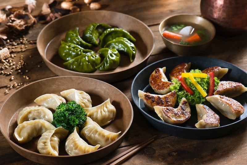 Three dishes of Chinese dumplings and soup on table