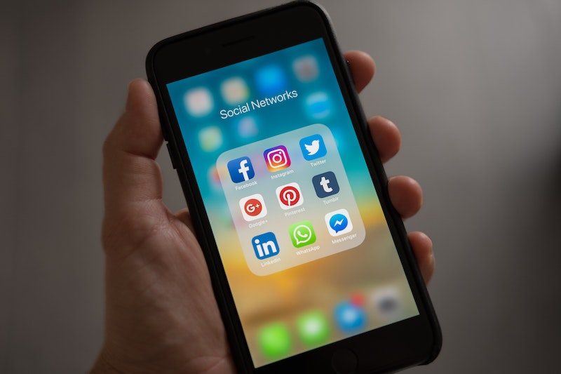 Man holding iPhone with social media apps