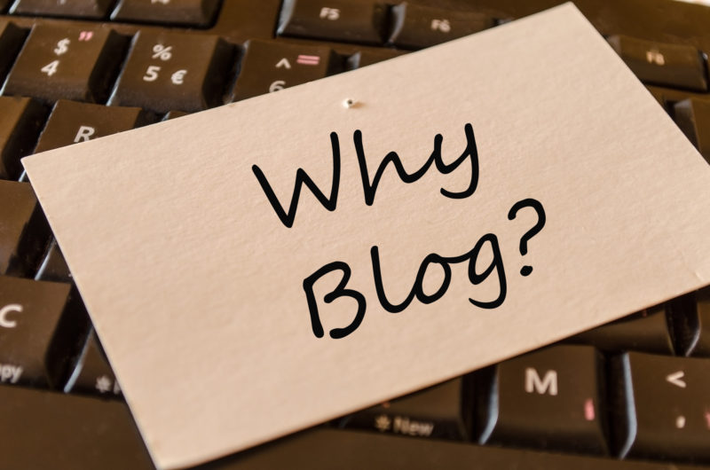 Why Blog? written on light brown card on keyboard